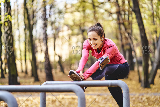 Young female jogger stretching her leg on bicycle stand in autumn forest