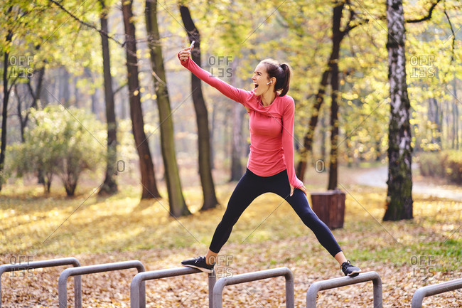 Young female jogger taking a selfie on bicycle stand in autumn forest