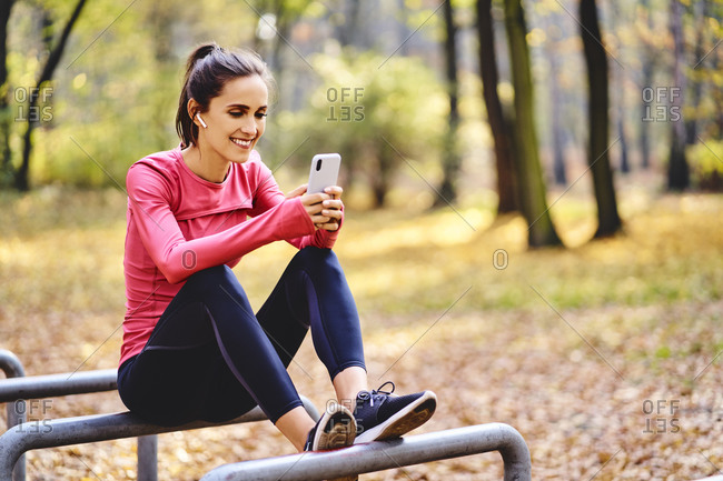 Young female jogger using smartphone on sitting on bicycle stand in autumn forest