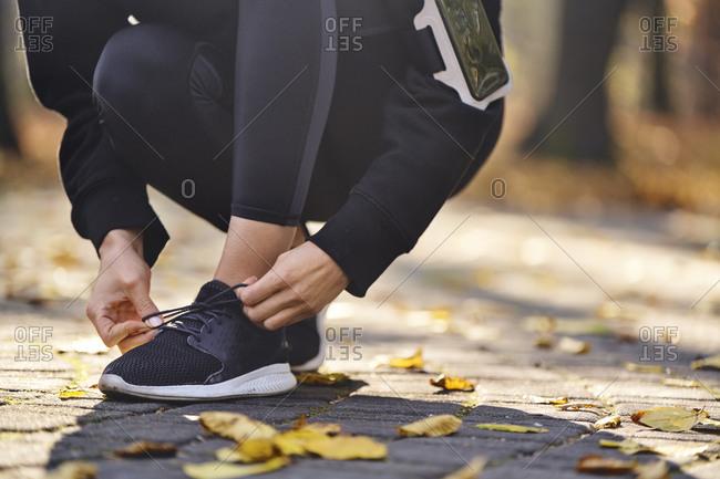 Young woman tying her running shoe