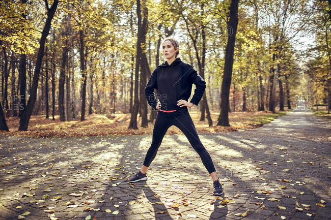 Young female jogger standing with open legs in autumn forest