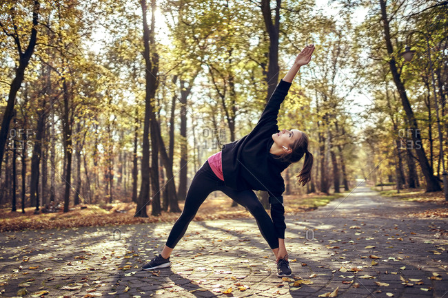 Young female jogger stretching her leg in autumn forest