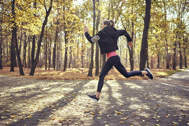 Young woman jogging in autumn forest