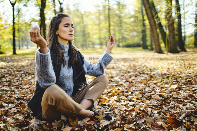 Young woman meditating in autumn forest