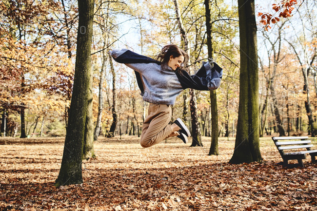Young woman jumping in autumn forest