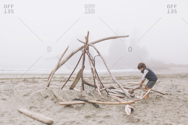 Boy arranging wood logs for campfire at beach during foggy weather