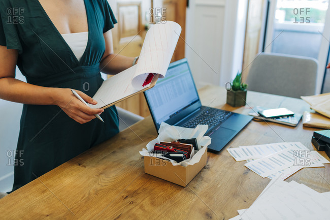 Midsection of female professional standing with clipboard at desk in office