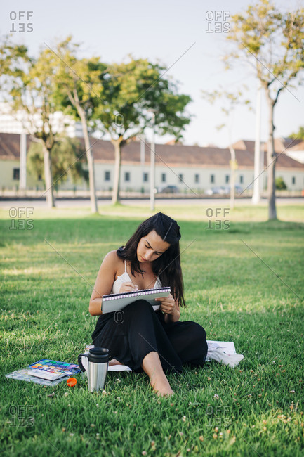 Young woman painting with watercolor in book while sitting in public park