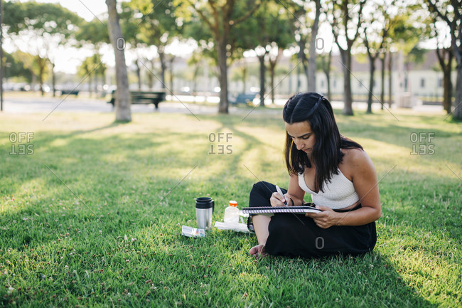 Young woman doing watercolor painting in book while sitting in park