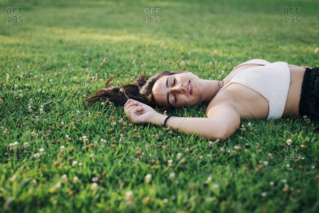 Woman napping while lying on grass at park