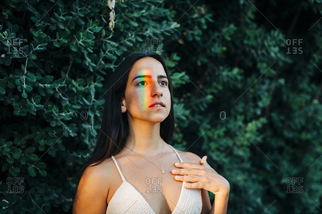 Young woman with multi colored light on face standing at park
