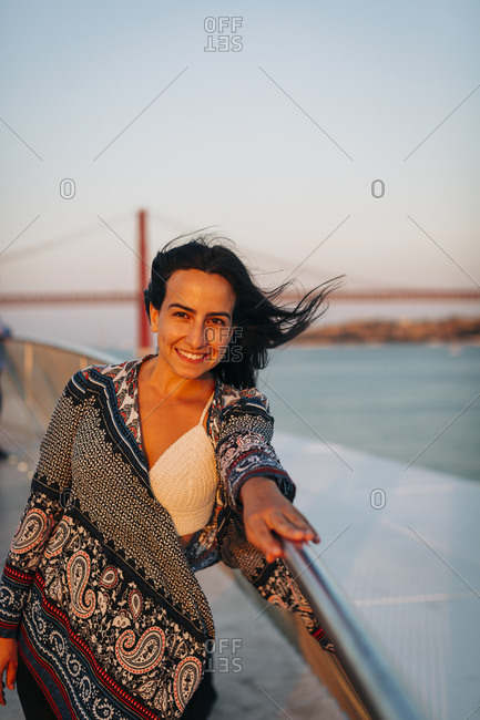 Woman smiling while leaning on retaining wall in city