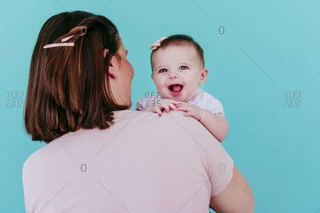 Mother and baby girl in front of turquoise wall
