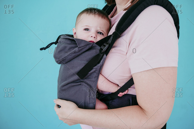 Mother and baby girl in baby carrier in front of turquoise wall