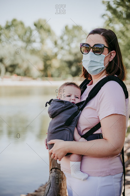 Mother and baby girl in baby carrier in park