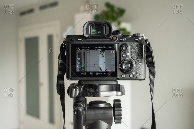 Close-up of digital camera on tripod in living room at home
