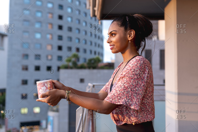 Beautiful woman holding coffee cup while standing in balcony enjoying sunset