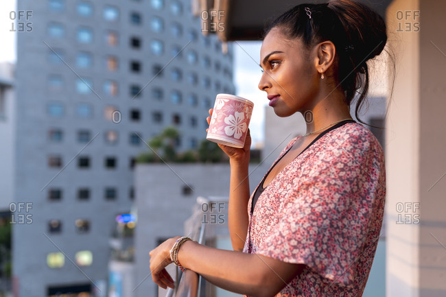 Beautiful woman standing in balcony while sipping coffee during sunset