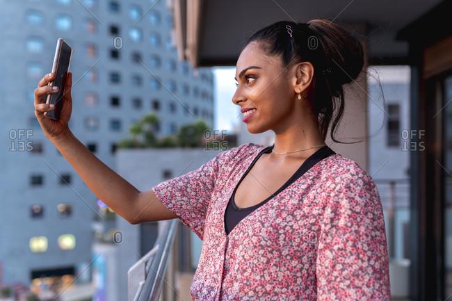 Beautiful smiling woman taking selfie in balcony