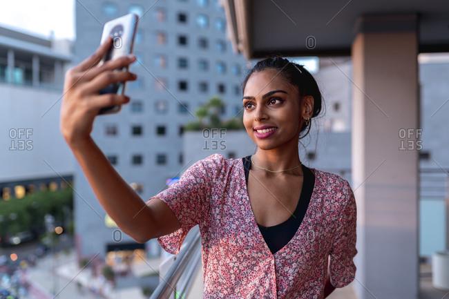 Happy woman taking selfie in balcony