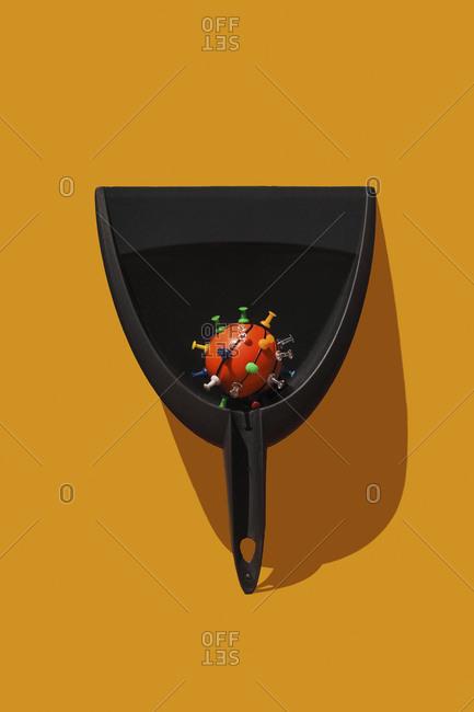 Studio shot of dustpan with thumbtacked basketball resembling virus cell