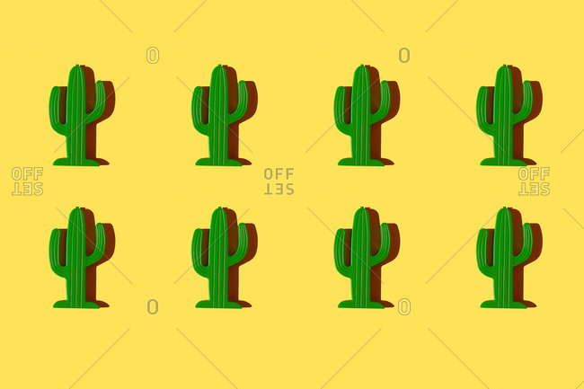 Pattern of small plastic cacti against yellow background