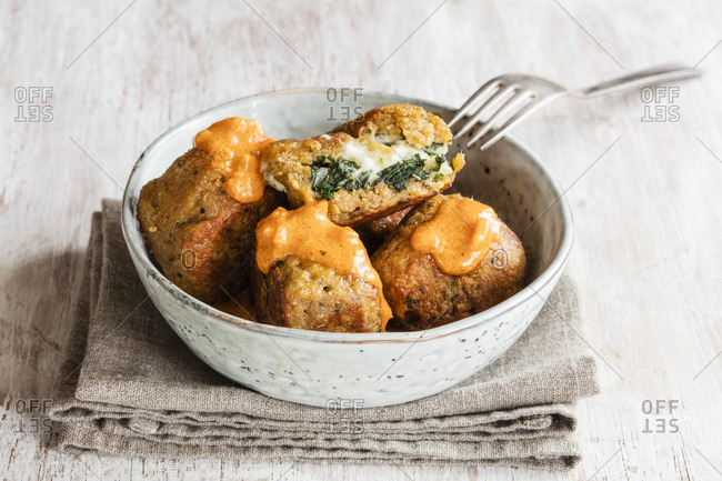 Bowl of fried spinach balls with tomato sauce