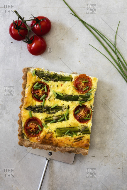 Slice of gluten free vegetarian buckwheat quiche with tomatoes- asparagus and chive