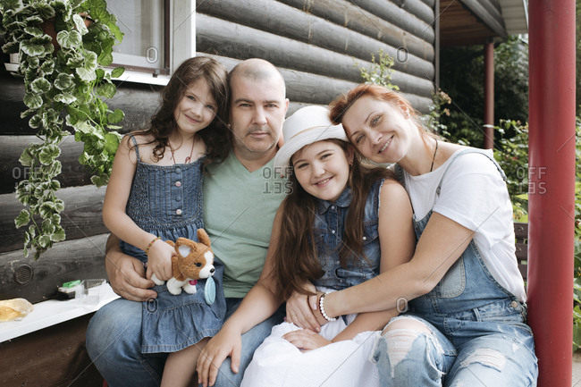 Happy family sitting on porch of house