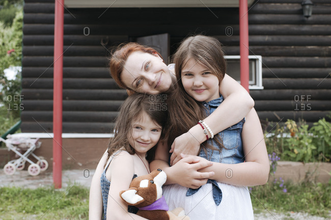 Happy mother with daughters at back yard against house