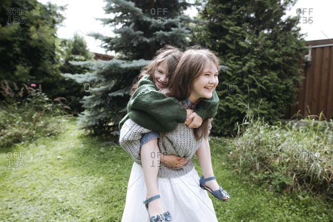 Girl giving piggyback ride sister in back yard