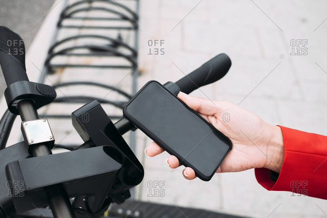 Hand of female professional scanning QR code on electric push scooter from smart phone