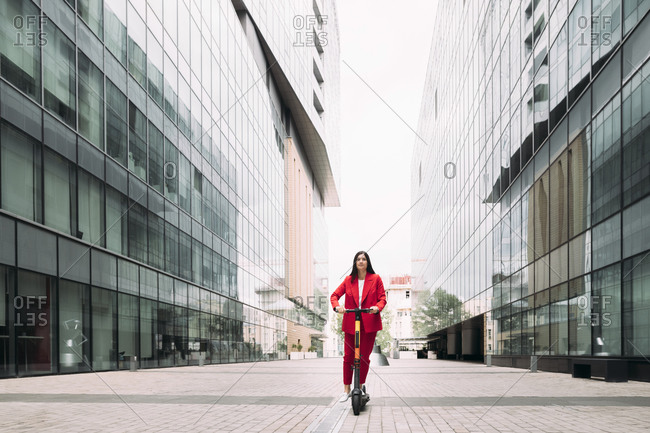 Female professional riding electric push scooter to commute in city