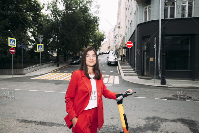 Beautiful businesswoman standing with electric push scooter against street in city