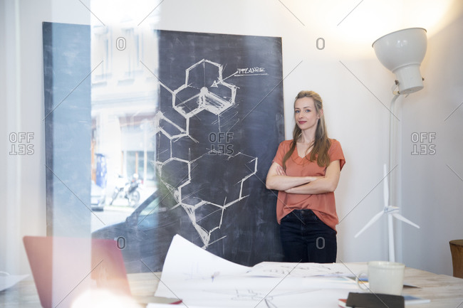 Confident woman standing at chalkboard with drawing in office