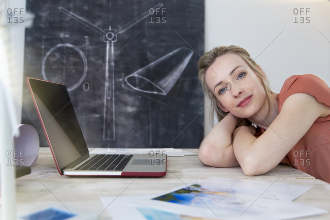 Portrait of confident woman leaning on desk in office