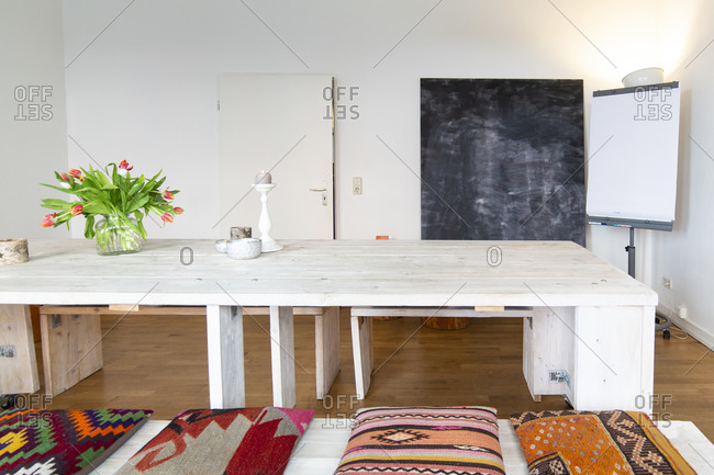 Room with wooden table- chalkboard and projection screen
