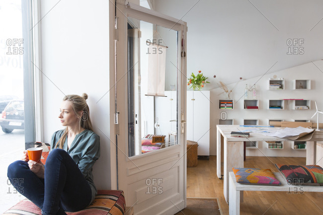 Relaxed woman having a break in home office looking out of window