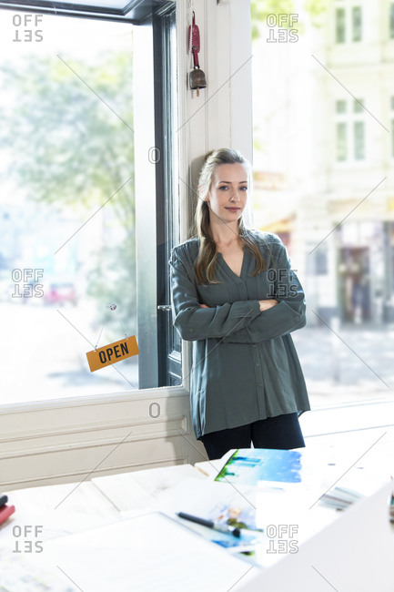 Portrait of woman leaning against glass door in office