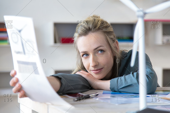 Portrait of woman leaning on desk in office with paper and wind turbine model