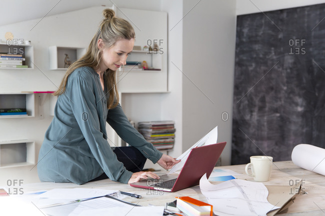 Woman using laptop on desk in home office