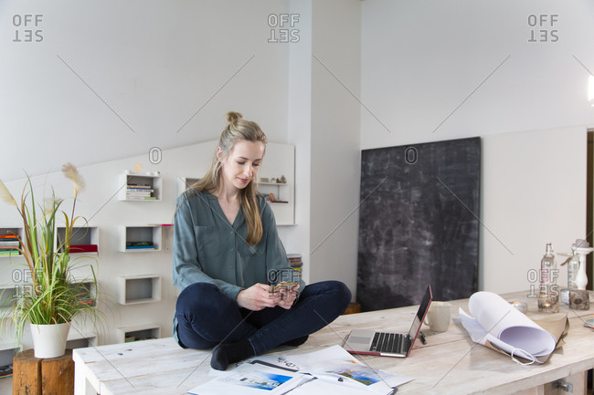 Woman sitting on desk in home office using smartphone