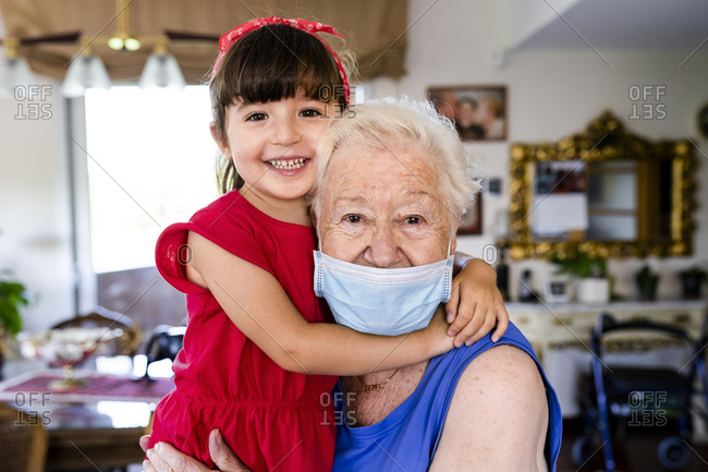 Grandmother and little girl spending family time together at home- with face mask