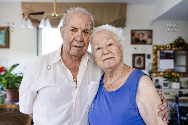 Senior couple looking at camera at home