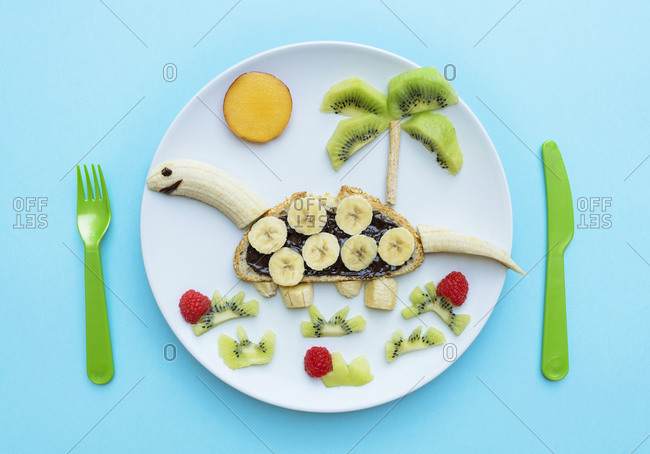 Breakfast with dinosaur shape made of banana- kiwi- bread- chocolate spread and berries on white plate on blue background