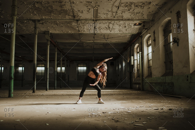 Woman stretching while exercising at abandoned factory