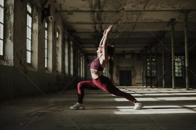 Woman practicing Anjaneya Sana yoga at abandoned factory