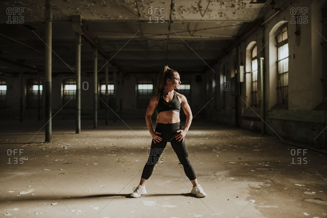 Muscular build woman standing with hand on hip at abandoned factory