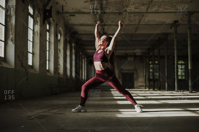 Smiling woman doing crescent lunge exercising at abandoned factory