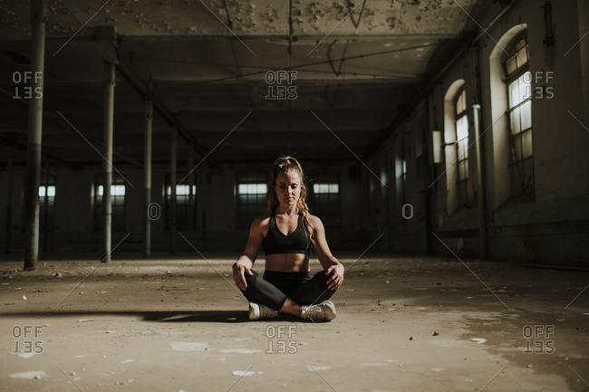 Athlete meditating while sitting at abandoned factory